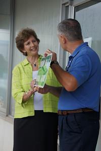10 08-14  Representative of State of Alabama Randy ______ presents a copy of Millard Fuller Memorial Highway sign to Linda Fuller.  s ferguson
