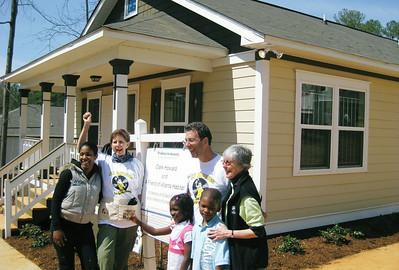 Larrie Del Martin, Executive Director of Atlanta Habitat for Humanity with Linda Fuller, Clark Howard and Gibbens family