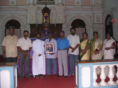 2009 - 02-28 Trivantrum Fuller Center Board at the Altar after the Requiem Mass. l-R: Abraham Mathew (treasurer), N. Vijayan (director), Fr. Mathew Thundathil (vice chair), K. Johnson - holding Millard's portrait (secretary), T H Lawrence (Chair), B. Beddyson (joint secretary, Elsamma Jacob (director), Cicily (mother-in-law of Lawrence's son, Shelly who lives in Texas) and Jessie (Lawrence's wife). T H Lawrence