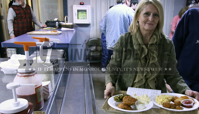 Gina Maness of Millstadt takes her order to her table at the Millstadt Sports Club.