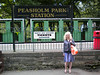 Liz stands by the <br /> <br /> Peasholm Park Station sign <br /> <br /> one end of the North Bay Railway <br /> <br /> We caught the train here for the ride to <br /> <br /> Scalby Mills Station