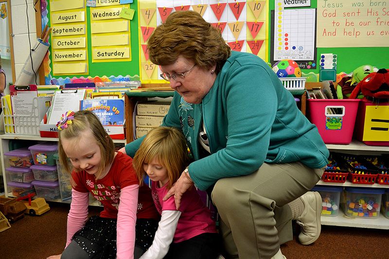 Kindergarten teacher Sister Nancy Wolf helps Bridget Fullenkamp, left, and Kaitlyn Muhlenkamp during free time at Immaculate Conception School in Celina.