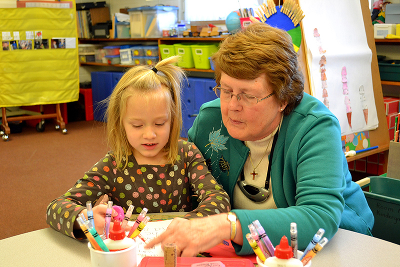 Kindergarten teacher Sister Nancy Wolf works with Cora Schumm at Immaculate Conception School in Celina, Ohio.