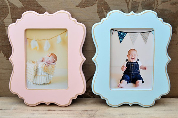 "5x7 ""ornate"" frames in pink and blue.<br /> <br /> Frames are handmade with pressed wood and a cost of satin finish for protection.  Distressed wood, by nature, will have minor imperfections which lend to the vintage feel of the frame."