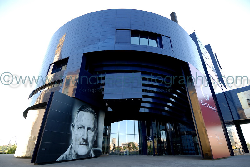 "<font size=""2"" face=""Verdana"" font color=""#5CB3FF"">View of the the Guthrie with Sir Tyrone Guthrie looking out onto the plaza area.  August 2007</font>"