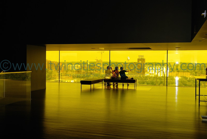 """<font size=""""2"""" face=""""Verdana"""" font color=""""#5CB3FF"""">Visitor to the Dowling Studio enjoying the view of the Mississippi Riverfront  through the amber colored glass in the lobby area.</font>"""
