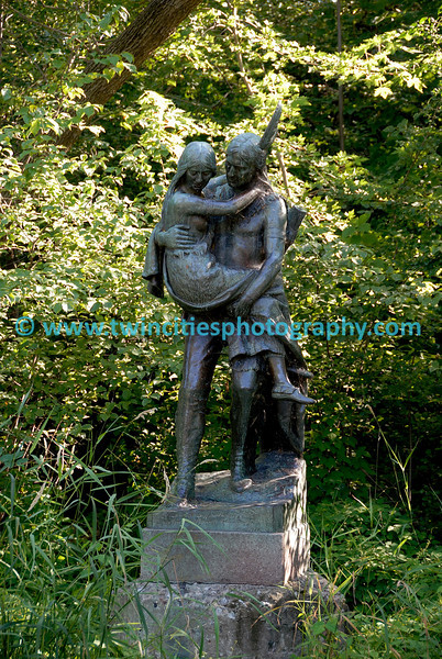 """#6424 - The life-size bronze sculpture by Jakob Fjelde (also of Ole Bull and Minerva fame) depicts Hiawatha and Minnehaha, characters from the poem """"Song of Hiawatha"""" by Henry Wadsworth Longfellow. It bears the inscription: <br /> Over wide and rushing rivers <br /> In his arms he bore the maiden. <br /> On exhibit at the Chicago World's Fair in 1893, the sculpture was purchased with pennies donated by school children in Minnesota – an effort organized by Mrs. L.P. Hunt of Mankato – and dedicated in 1912. The sculpture, which rests on a small island in the creek, can be viewed from the water's edge a short way above the falls."""