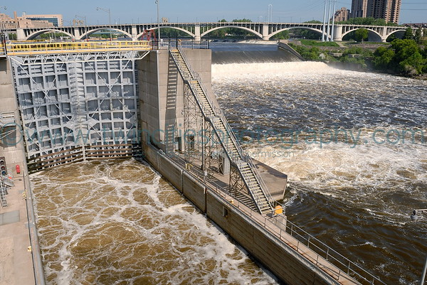 View of the lock and dam on the Mississippi River with St. Anthony Falls next to the lock.  The lock is in the process of draining as evidenced by the turbulent water.