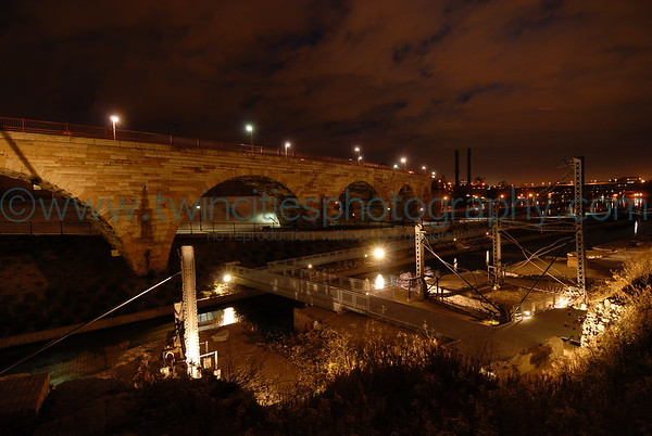 Night time view of the Stone Arch Bridge with the mill ruins area along the banks of the Mississippi.