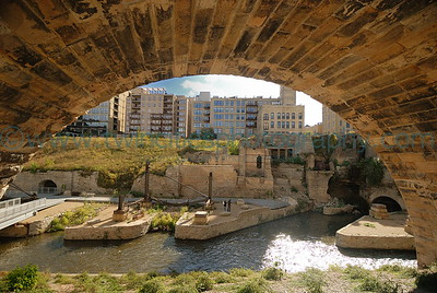 The historic mill ruins area as viewed through one of the arches of the Stone Arch Bridge.  New high-end condos are also visible on the bluff.