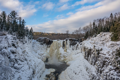 "PIGEON RIVER 04203  ""High Falls - Freezing Up!""  December 22, 2016 - Here is what High Falls of the Pigeon River in Grand Portage State Park currently looks like.  There has been a lot of ice development on the waterfall thanks to the week of very cold temperatures we just had.  There is, however, still one large channel of running water right in the middle of the waterfall.  This photo was taken late in the day just as the sun was setting to the west (the view here is looking north).  I really liked the clouds on this day and the way they mirrored the angle of the line of trees on the right side of the photo."