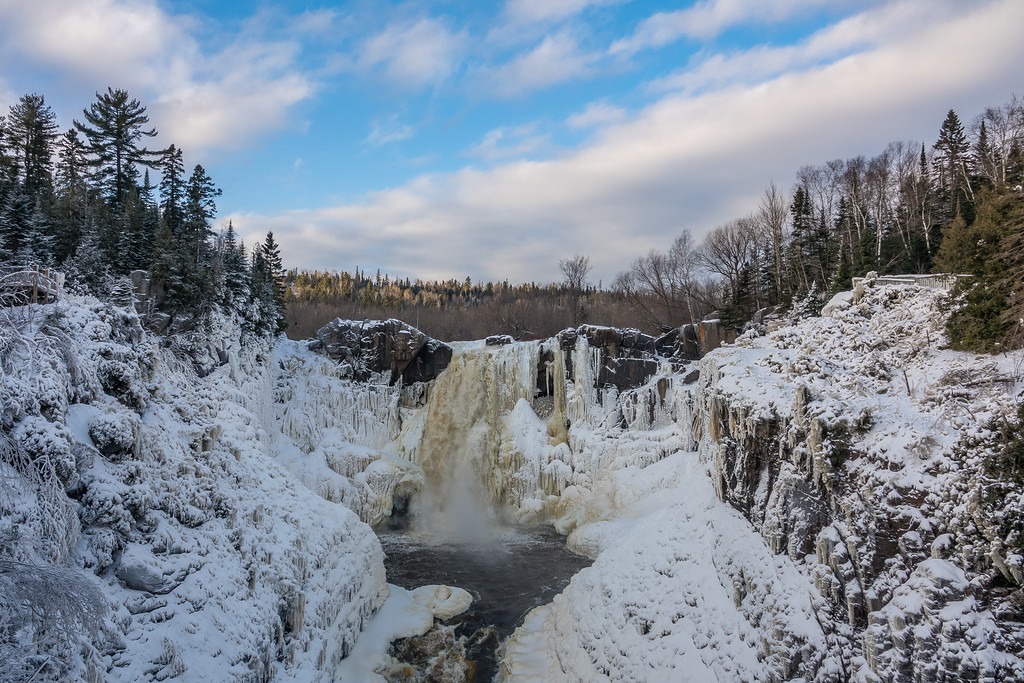 """PIGEON RIVER 04203<br /> <br /> """"High Falls - Freezing Up!""""<br /> <br /> December 22, 2016 - Here is what High Falls of the Pigeon River in Grand Portage State Park currently looks like.  There has been a lot of ice development on the waterfall thanks to the week of very cold temperatures we just had.  There is, however, still one large channel of running water right in the middle of the waterfall.  This photo was taken late in the day just as the sun was setting to the west (the view here is looking north).  I really liked the clouds on this day and the way they mirrored the angle of the line of trees on the right side of the photo."""
