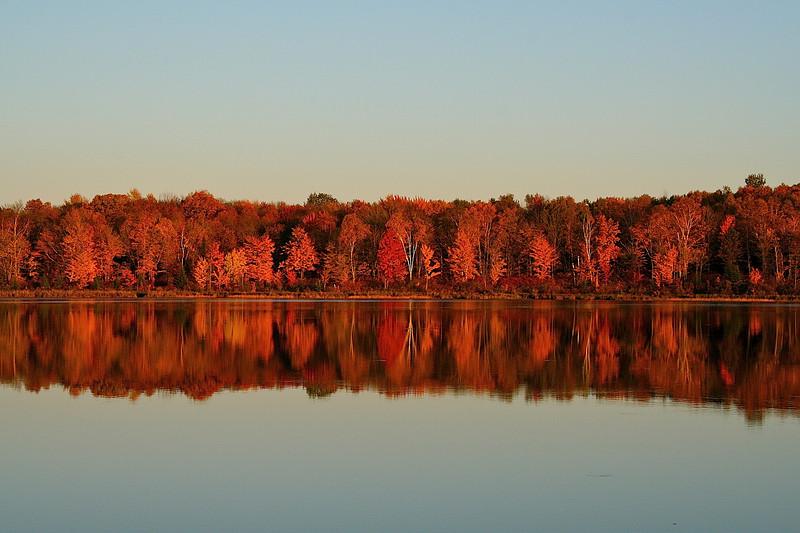 Fall sunset on still water.