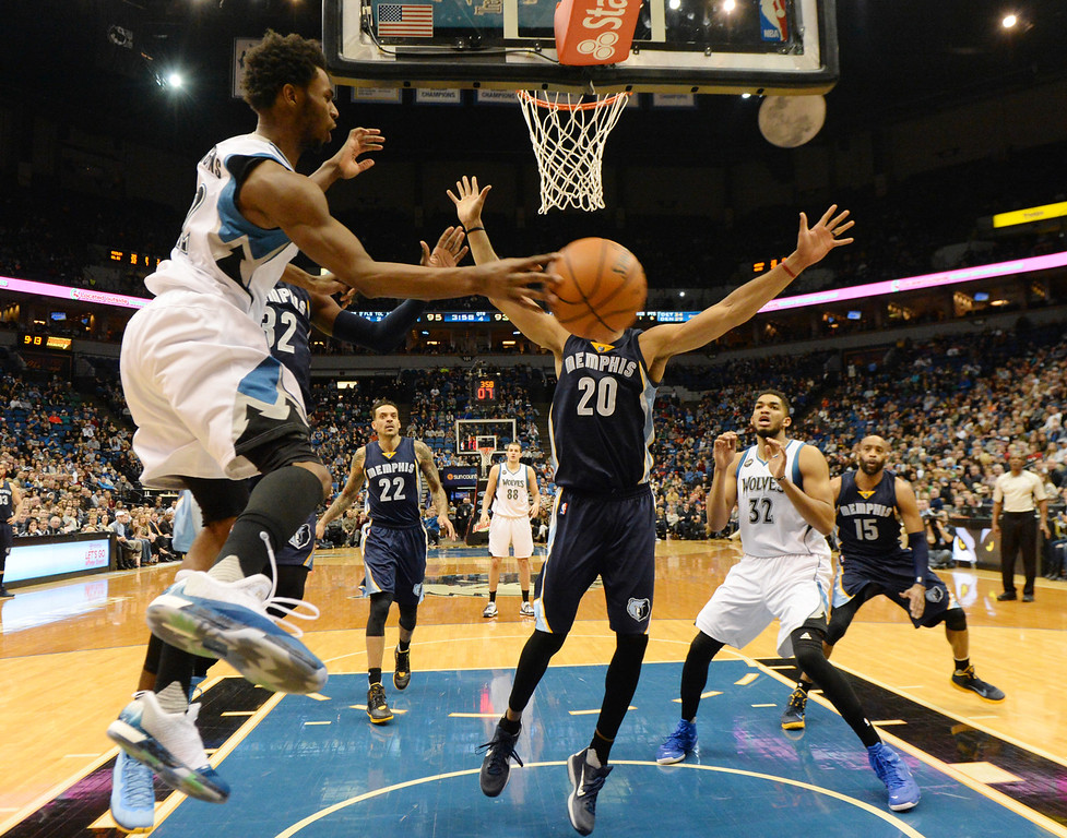 . Minnesota Timberwolves guard Andrew Wiggins pass the ball around Memphis Grizzlies center Ryan Hollins toTimberwolves center Karl-Anthony Towns in the second half at the Target Center on Saturday, January 23, 2016. (Pioneer Press: John Autey)