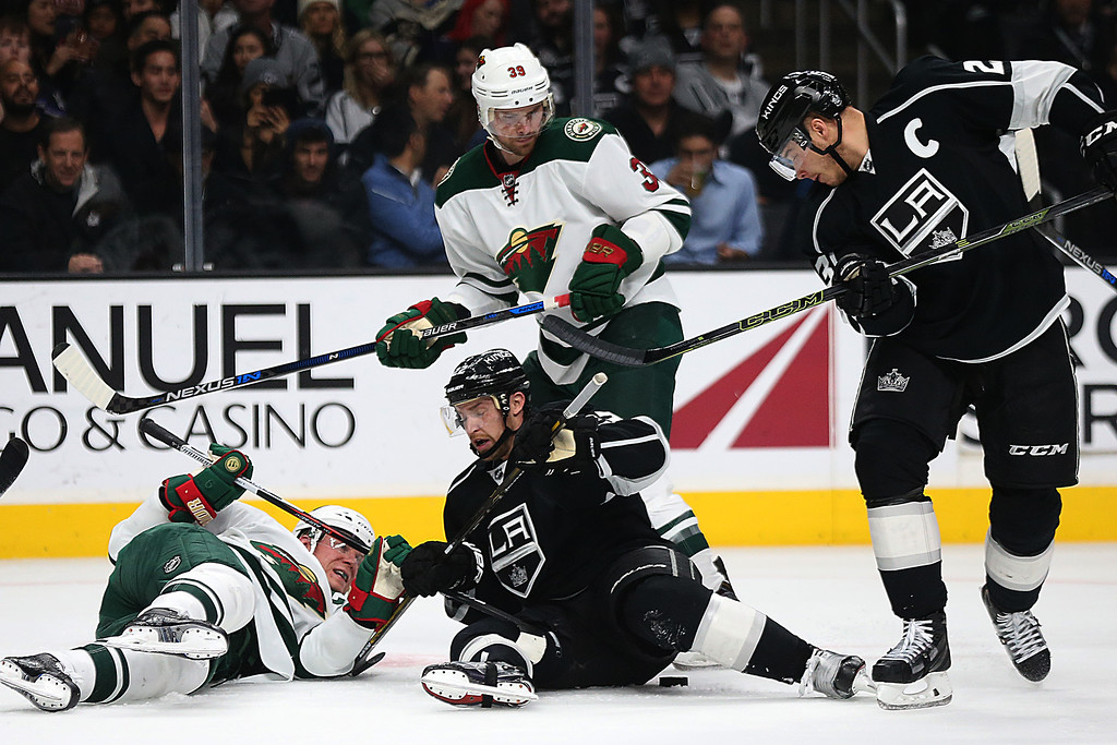 . The Los Angeles Kings\' Trevor Lewis, middle, and the Minnesota Wild\'s Miko Koivu, left, fall to the ice as they try to control the puck during the first period at Staples Center in Los Angeles on Thursday, Jan. 21, 2016. (Robert Gauthier/Los Angeles Times/TNS)