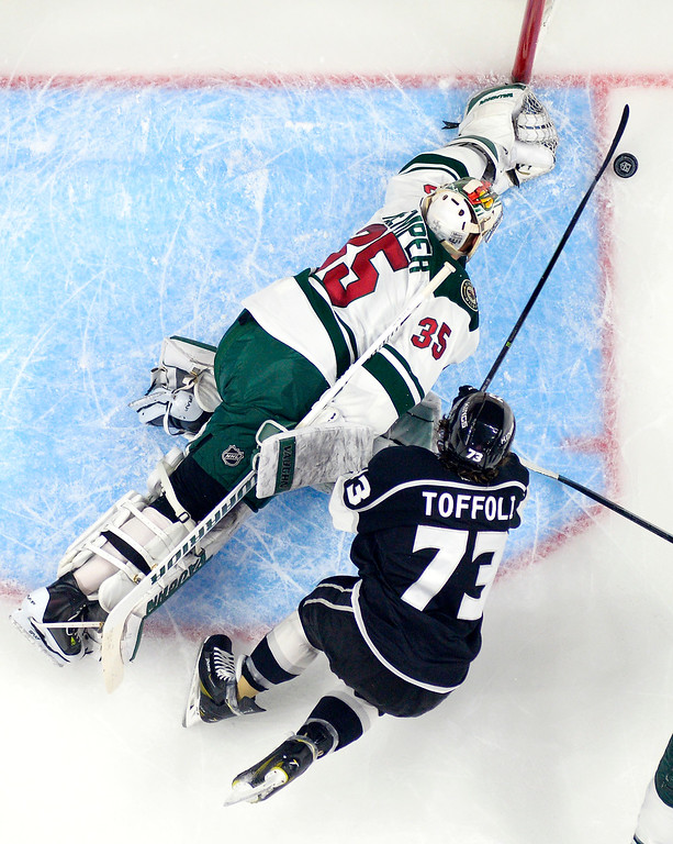 . Los Angeles Kings center Tyler Toffoli, right, tries to get a shot in on Minnesota Wild goalie Darcy Kuemper during the first period of an NHL hockey game Thursday, Jan. 21, 2016, in Los Angeles. (AP Photo/Mark J. Terrill)