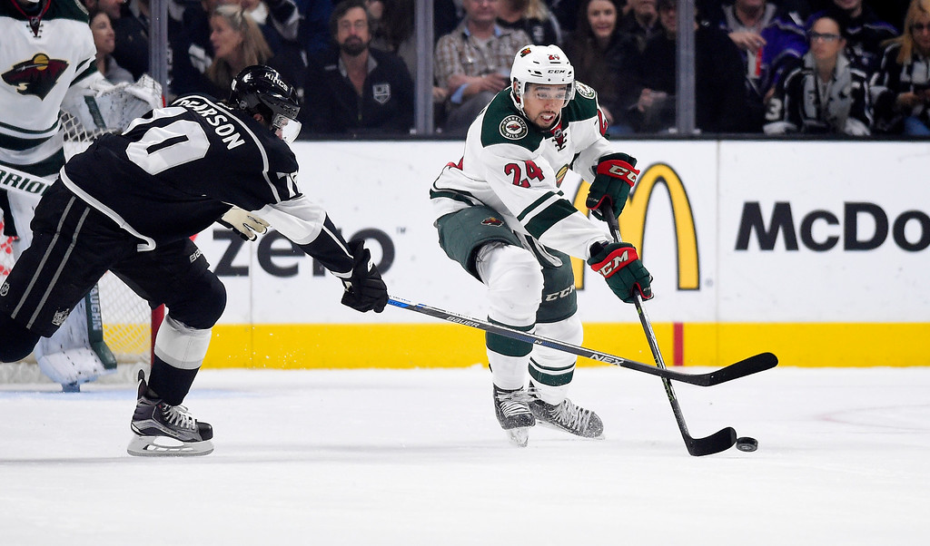 . Minnesota Wild defenseman Matt Dumba, right, moves the puck as Los Angeles Kings left wing Tanner Pearson reaches in during the first period of an NHL hockey game Thursday, Jan. 21, 2016, in Los Angeles. (AP Photo/Mark J. Terrill)