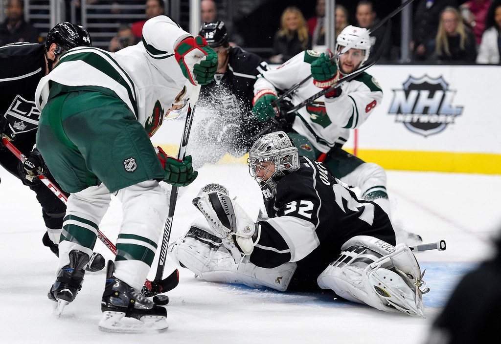 . Minnesota Wild left wing Chris Porter, left, tries to get a shot in on Los Angeles Kings goalie Jonathan Quick, center, as defenseman Marco Scandella stands behind during the first period of an NHL hockey game, Thursday, Jan. 21, 2016, in Los Angeles. (AP Photo/Mark J. Terrill)