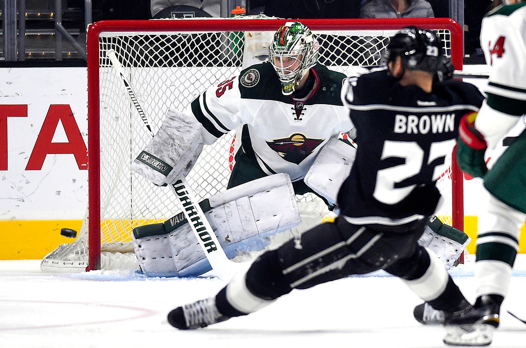 . Los Angeles Kings right wing Dustin Brown, right, shoots the puck as Minnesota Wild goalie Darcy Kuemper defends the goal during the first period of an NHL hockey game, Thursday, Jan. 21, 2016, in Los Angeles. (AP Photo/Mark J. Terrill)