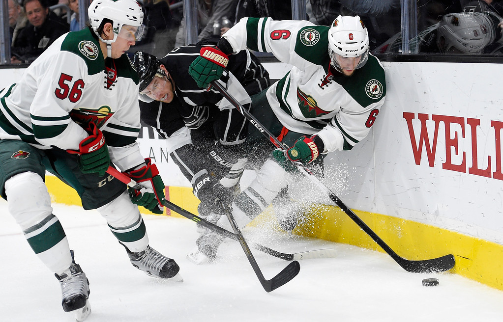 . Los Angeles Kings center Jeff Carter, center, battles for the puck with Minnesota Wild left wing Erik Haula, left, of Finland, and defenseman Marco Scandella during the second period of an NHL hockey game Thursday, Jan. 21, 2016, in Los Angeles. (AP Photo/Mark J. Terrill)