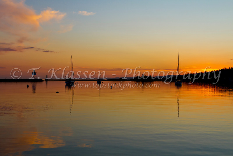 Sailboats anchored in the calm water of the harbor at sunset in Grand Marais, Minnesota, USA.