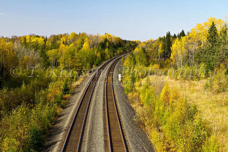A train track running through brilliant fall foliage color in northern Minnesota, USA.