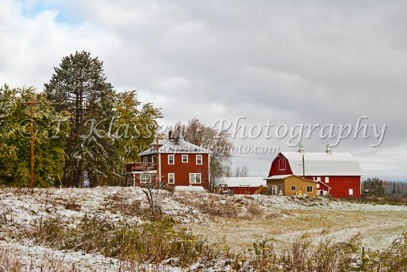 A farm with red buildings and first snowfall near Floodwood, Minnesota, USA.