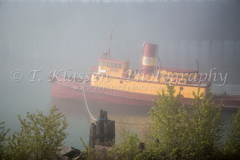 A vintage tugboat Edna at iron ore docks and loading facility in the fog at Two Harbors, Minnesota, USA.