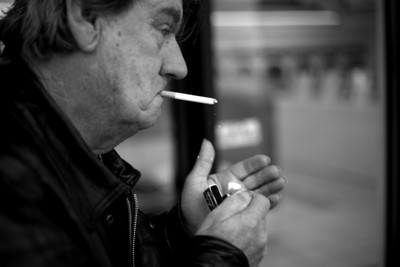 Minor James Miller Junior lights a cigarette outside of the Courtesy Cleaners on Broadway Avenue in Mattoon, Illinois on December 12, 2009.  Miller smokes about two packs a day as a way to kill time.   (Jay Grabiec)