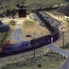 Train crossing Caliente Bodfish Road on the La Mesa HO-scale club.<br /> May 1985.