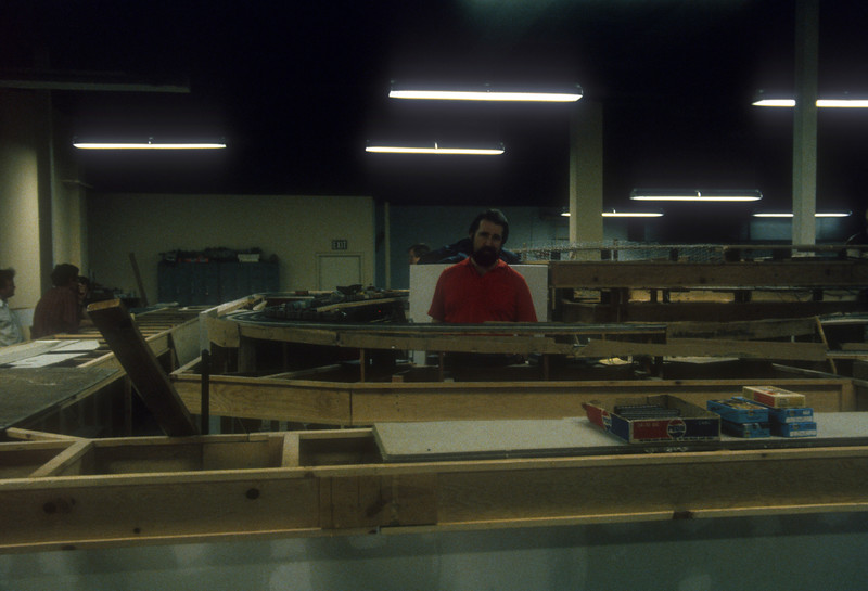 Dave Hussey amid the benchwork at the west end of the San Diego Model RR Ass'.n HO-scale club.<br /> May 1985.