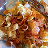 Salad of tomato, lettuce, cheese Fritos and Catalina dressing
