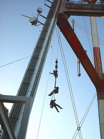 Three men descending Sutro Tower by rope