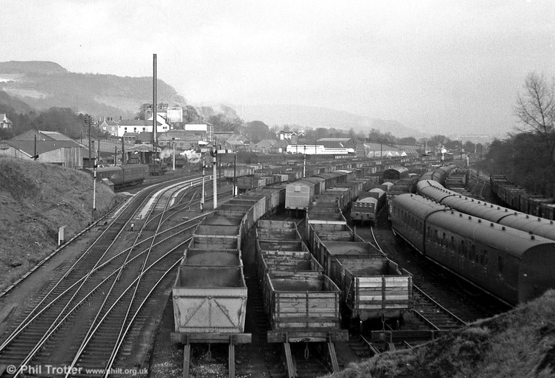A steam era view of Neath and Brecon Junction. The line ahead (left) led to Brecon via Onllwyn, that branching to the right to Glynneath and Hirwaun. In the distance, a number of 0-6-0 pannier tanks can be seen on the (NBR) shed. The shed closed in 1964 and houses, Halfords and Burger King now stand on the site.