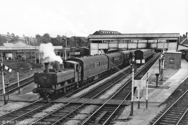 Western Region 0-6-0PT 7444 shunts a mail train at Carmarthen. 7444 was outshopped in February 1950 and spent its entire life in the Carmarthen and Llanelli areas until withdrawn in July 1964. Carmarthen shed (87G) is visible in the background, beyond the footbridge.