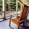 d/l of hotel porch, railing and rocking chairs