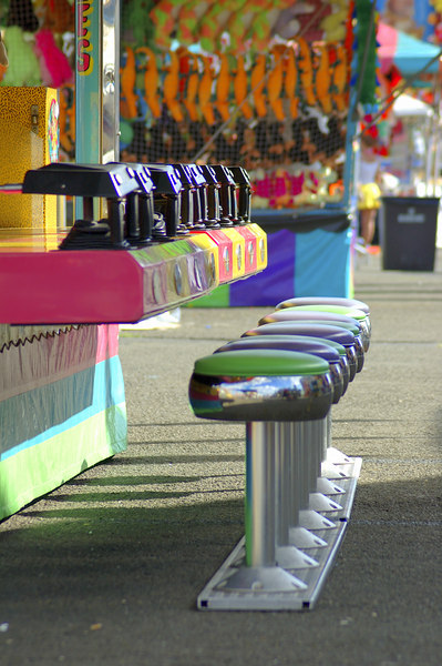 A row of stools at a Carnival Midway game.  There are long shadows and rows of colorful prizes in the backgroundK