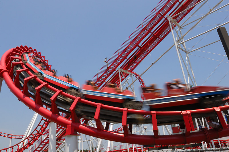 Red Steel Roller Coaster with cars flashing by.  The cars are blurred.  There is a cloudless blue sky.