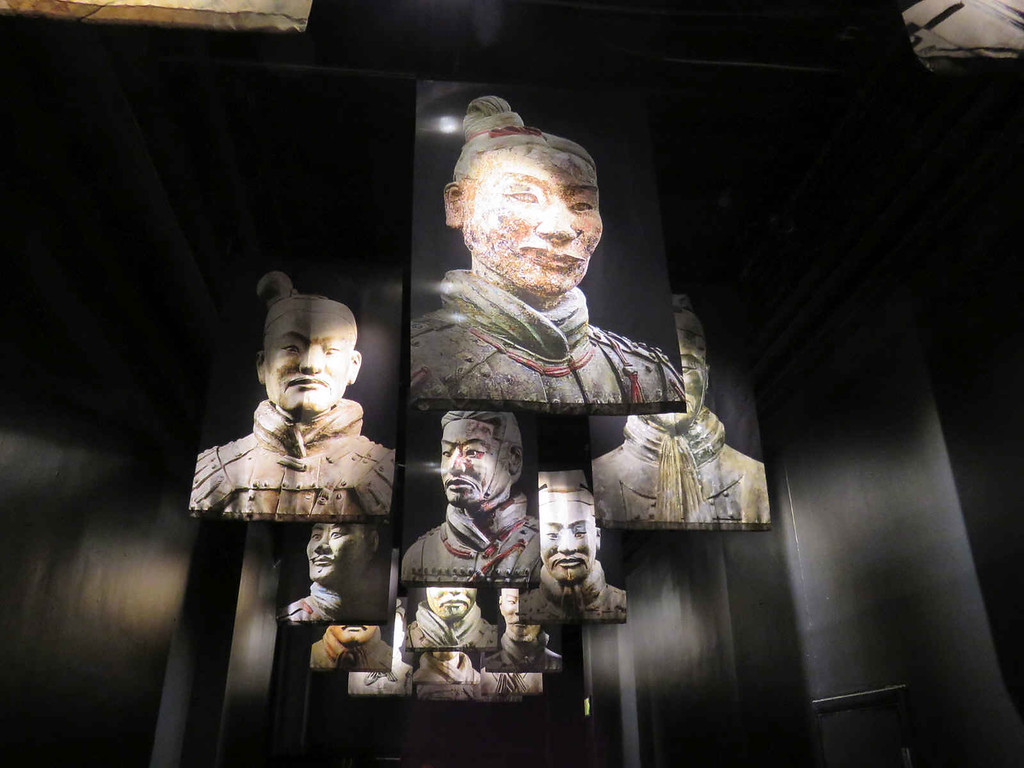 portraits of terracotta warriors in the hallway between exhibit sections