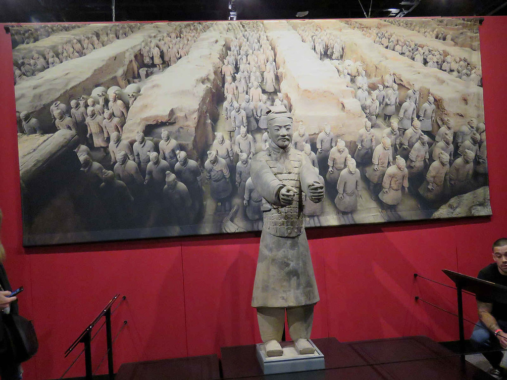 charioteer in front of a painting showing the terracotta warriors in place