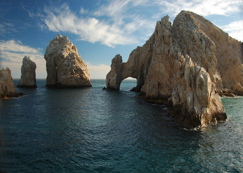 Los Arcos in Cabo San Lucas at Sunset.  There is a blue sky with wispy clouds.