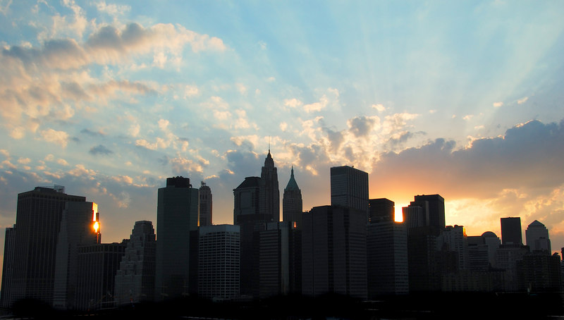 Downtown Manhattan Skyline with sunset.  There are rays of light emerging from behind the buildings.  The buildings are silhouetted with a small amount of shadow detail.  There are clouds and blue sky.
