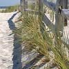Sunny Seaside Fence with grass and long shadows.  The sky is blue and cloudless.  The sand is white.