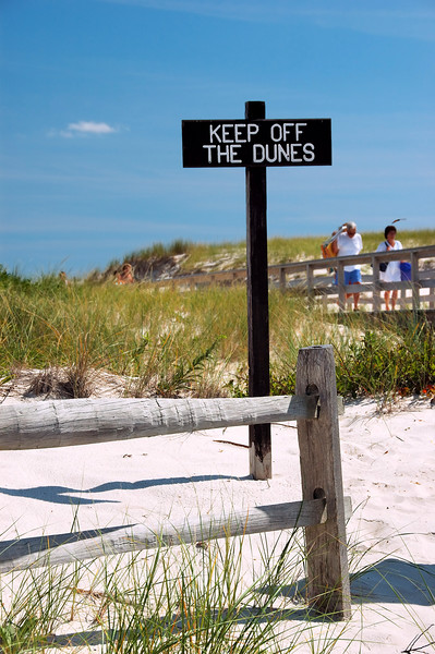 Beach scene with fence and sign that says Keep off the Dunes.  There is sand, grass and a blue sky.  There are people visible in the blurred background.