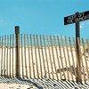 Beach scene with fence and sign that says keep of the dunes.  The sign is weathered.   There is a blue sky with a few clouds