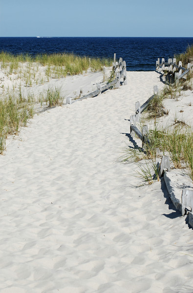 White Sandy Path to the Beach.  The sky is cloudless and blue.  The ocean is a very deep blue.  There is a boat on the distant horizon.