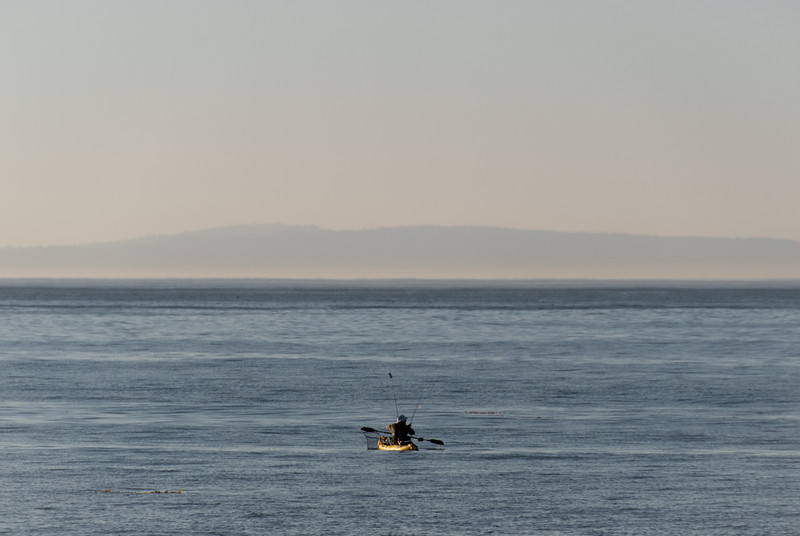 """<span id=""""title"""">Fishing</span> This guy sure had a small boat... but the water was very calm so I suppose it's OK. I'm sure he knew what he was doing. Palos Verdes peninsula in the background."""
