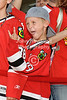 A young Blackhawk fan on the red carpet is pumped up for the home opener NHL game between the Chicago Blackhawks and the Dallas Stars at the United Center in Chicago, IL.