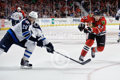Chicago right wing Michael Frolik (67) fires a shot past Winnipeg defenseman Johnny Oduya (29) during the NHL game between the Chicago Blackhawks and the Winnipeg Jets at the United Center in Chicago, IL. The Blackhawks defeated the Jets 4-3.