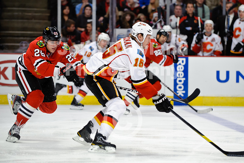 Calgary right wing Tim Jackman (15) brings the puck up ice past Chicago left wing Viktor Stalberg (25) during the NHL game between the Chicago Blackhawks and the Calgary Flames at the United Center in Chicago, IL. The Blackhawks defeated the Flames 4-2.